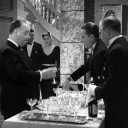 L'apparition d'Hitchcock: AIfred Hitchcock apparaît durant la soirée des Sebastian en invité goulu : il vide avidement une flûte de champagne. On peut y voir un clin d'œil autobiographique : ce n'était un secret pour personne qu'Hitchcock aimait bien boire et bien manger. Mais plus encore, c'est sa position de maître du suspense que le réalisateur revendique par cette apparition : en vidant son verre, il ne fait qu'augmenter le risque de voir Alexander Sebastian descendre à la cave, et il renforce donc le suspense de la scène. Hitchcock - (NOTORIOUS – Alfred Hitchcock, 1946)